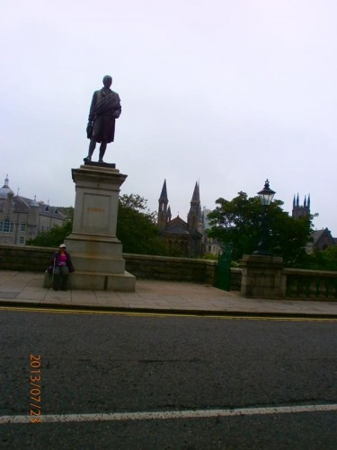 Tatiana sitting in front of a bronze statue of Scotland's most famous poet and lyrist Robert Burns on Union Terrace.