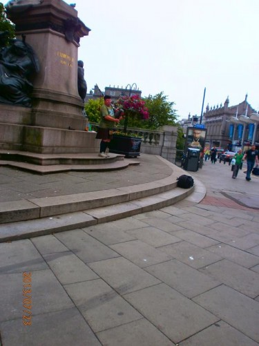 A man playing bagpipes next to a statue of King Edward VII on the corner of Union Street and Union Terrace.