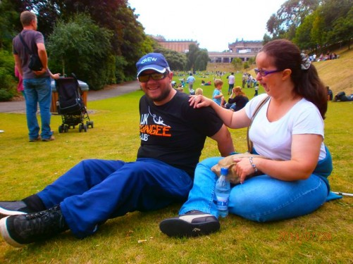 Tatiana and Tony sitting on the grass in another part of Princes Street Gardens. Lots of other people also relaxing on the grass.
