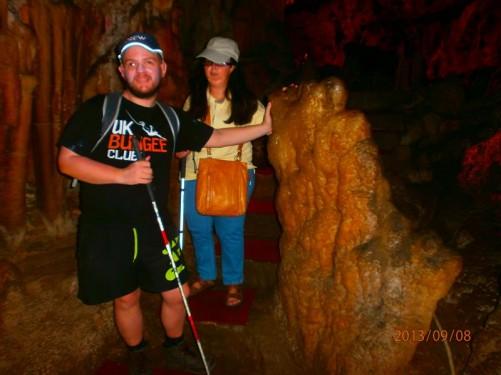 Tony and Tatiana touching a big stalagmite.
