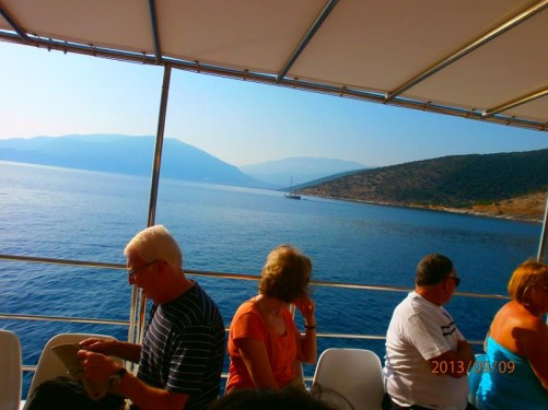 Now at sea. Fellow passengers sitting in front. View over the sea towards land, possibly the island of Ithaki (Ithaca), which is north-east of Kefalonia across a narrow strait.