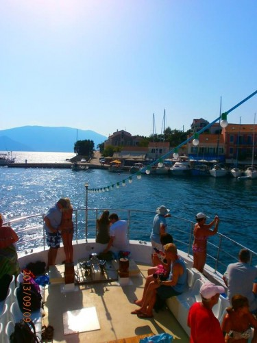 In Fiskardo harbour. Towards the bow of the boat with other passengers.