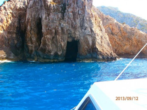 """Now back on the boat looking at the entrance to a sea cave in a cliff. There are several """"Blue Caves"""" cut into cliffs around Cape Skinari on Zakynthos's north coast."""