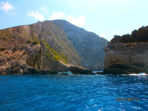 Another picturesque view from the boat. Looking into a bay with high uneven cliffs. Rocks protruding from the water.