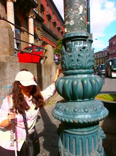 Tatiana touching the flamboyantly decorated base to a lamp post. The metal moulding includes lion's heads, leaf patterns and geometric decoration.