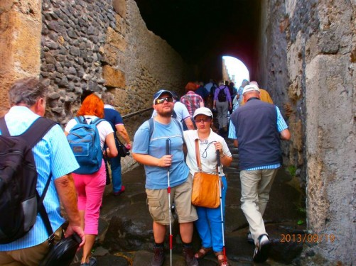 Tony and Tatiana at the main entrance gate. They are at the bottom of a sloping covered passageway. The stone surface is rough with some steps. Lots of visitors are making their way up.