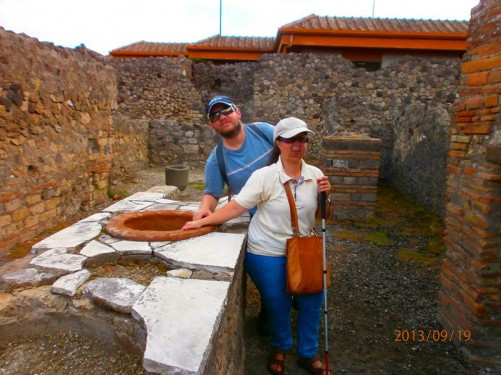 Tony and Tatiana touching a low wall with a series of large holes built into the top. This wall was used as a counter to sell food and drink, known as a thermopolium. It is topped with marble. The holes held terracotta containers.