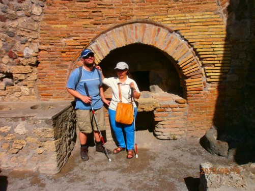 Inside a Roman bakery with a walled oven behind. Part of the Pistrinum (mill). There were also large flour grinders to the side.