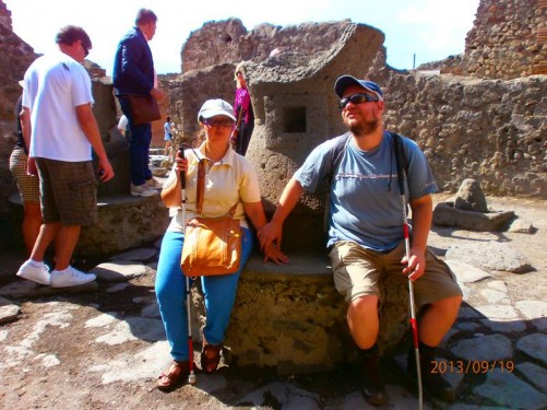 Tatiana and Tony sitting on a round stone base. Perhaps the base of a column or some sort of pedestal.