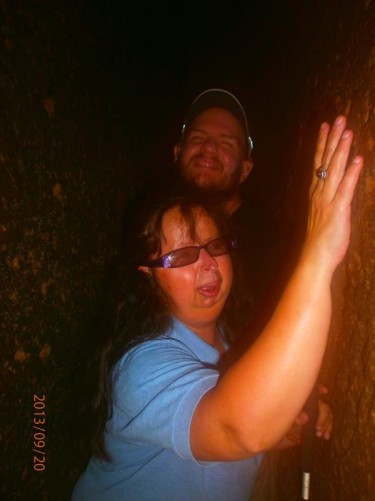 Tatiana and Tony squeezing along an extremely narrow passage between stone walls.