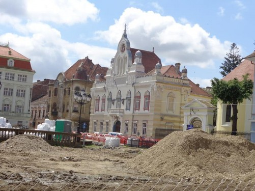 View towards the south-west corner of Union Square (Piața Unirii). The centre of the square is undergoing reconstruction and is fenced off. The building directly in front is the Serbian Orthodox Vicariate, which is baroque in style, and dates from the 18th century. To the right a small part of the Serbian Orthodox Cathedral can also be seen.