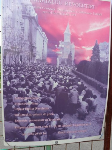 A poster for the Revolution Memorial (Memorialul Revolutiei) showing a large mass of protesters sitting in Victory Square. The Revolution Memorial is a museum documenting the 1989 uprising, which led to the overthrow of the communist regime of Nicolae Ceaușescu. The uprising started in Timișoara and led to 1,104 people being killed.