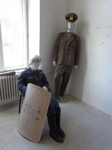 Models of two men in police or army uniforms dating from the time of the 1989 revolution. One holding a riot shield.