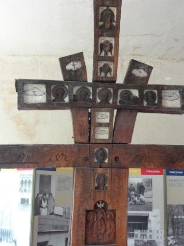 A large wooden cross with Christian icons carved on the front. Still inside the museum.