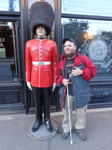 Tony outside the English-style King's Pub next to a life-sized model of a Queen's Guard in red tunic and bearskin hat.