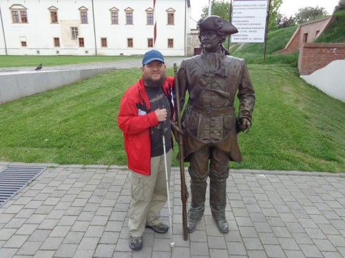 Tony by a life-sized bronze statue, probably of a soldier or guard. He is holding a long musket at his side.