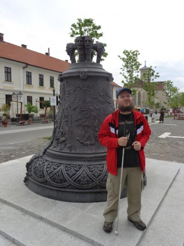 Tony by a large bell sitting in the middle of a square in Alba Iulia's upper town. There are a number of decorative human heads protruding from the top of the bell and the sides are decorated with reliefs depicting historic scenes.