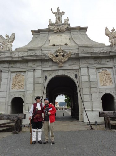 Tony standing outside 3rd Gate with a real man in historic guards' uniform and holding a musket. A drawbridge in front of the gate. This side of the gate is again topped with statues and has a double-headed eagle in the top middle.