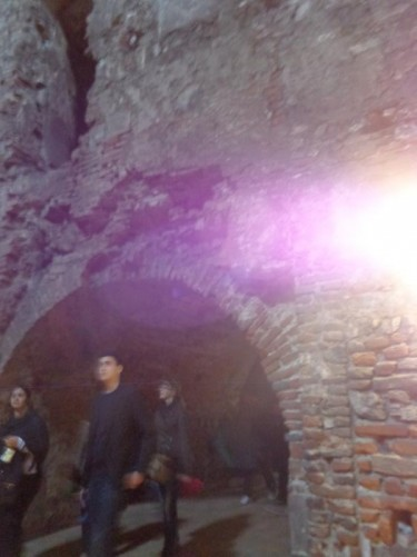 Visitors emerging from an arched tunnel built of brick.