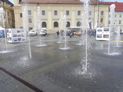 Back in Grand Square. In front, a series of fountains: simple jets of water shooting from the paved surface of the square.