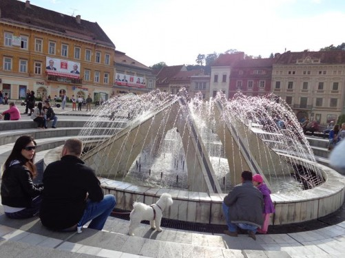 People sitting on steps around a large modern fountain in Council Square (Piaţa Sfatului), arguably the centre of Brașov. It has apparently held annual markets since 1364, being visited by merchants from the country and abroad. The square features medieval buildings in different architectural styles.