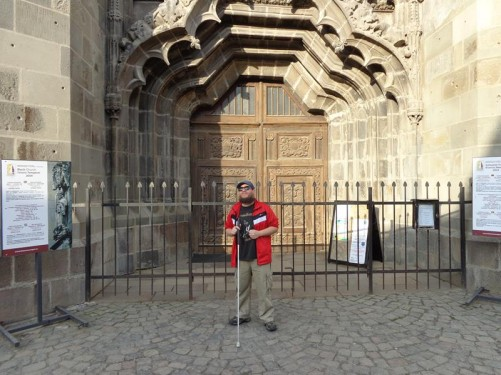 Tony in front of the main entrance into the Black Church. Large wooden double doors with a decorative stone surround.