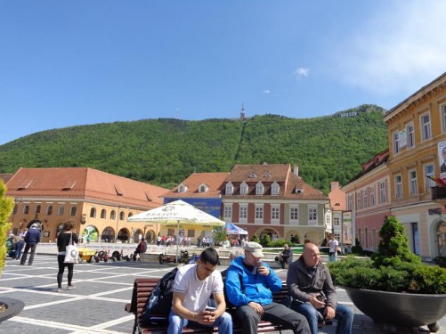 Another view across Council Square (Piaţa Sfatului). People sitting on a bench in the foreground. In the background, a good view of forested Tâmpa Hill. The hill sits at the edge of the city near the old town and rises to 960 metres (3,150 feet ) above sea level. There is a cable car to the top with excellent views over the city from the top.