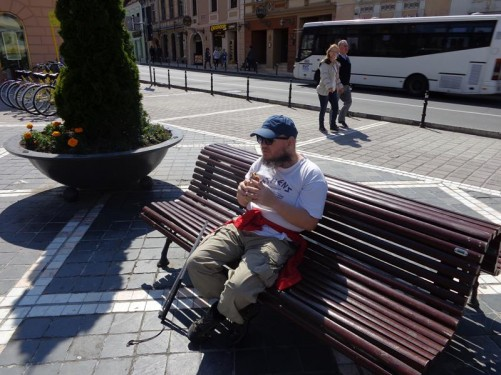Tony sitting on a bench in Council Square eating a sandwich.