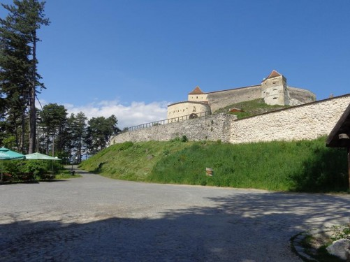 View looking up at the stone walls and towers of Râșnov Fortress from near the entrance. It sits on top of a rocky outcrop.