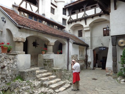 Interior courtyard. The walls are a mixture of stone and timber frame construction. Tony at the bottom of a flight of stone steps leading to a doorway.