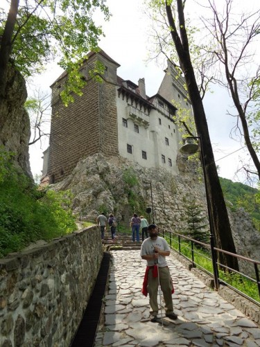 Tony on a steep path leading up to Bran Castle. A good view of the castle above, standing prominently on top of its rocky outcrop.