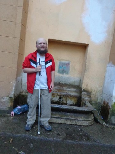 Tony in front of a small drinking fountain.