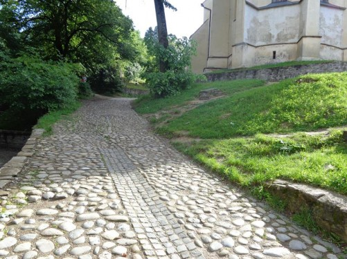 A steep narrow cobblestone road leading up to the Church on the Hill (Biserica din Deal). Only the lower walls of the church are in view.