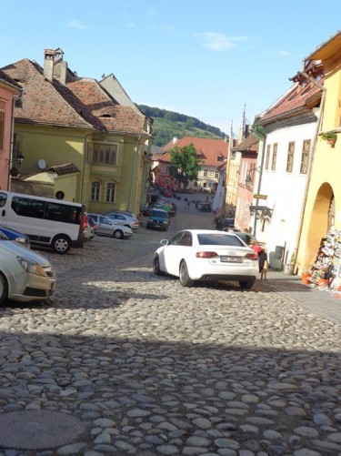 Looking down hill along a cobbled street with Citadel Square visible at the far end.