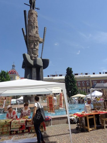 More market stalls in front of the fountain. The one in front selling rugs. The pillar and legs of the Avram Iancu statue can be seen behind.
