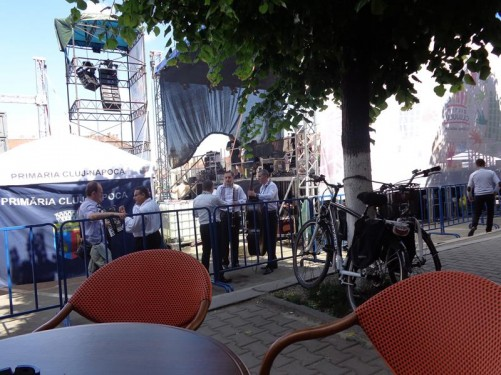 In Union Square looking towards the side of a large stage used for the Cluj Week musical performances. There are a group of musicians standing near the stage, holding instruments, including a double bass.