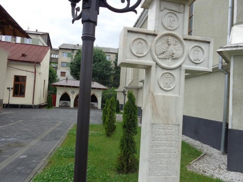A courtyard at the side of the Assumption of the Virgin church. A stone cross immediately in front.
