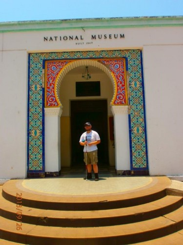 Tony standing outside a museum entrance. Colourful Islamic-style decorative tiles around the doorway.