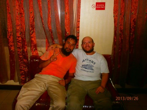 Tony sitting on a settee with another traveller from the Republic of China at the Safari Inn Ltd hostel.