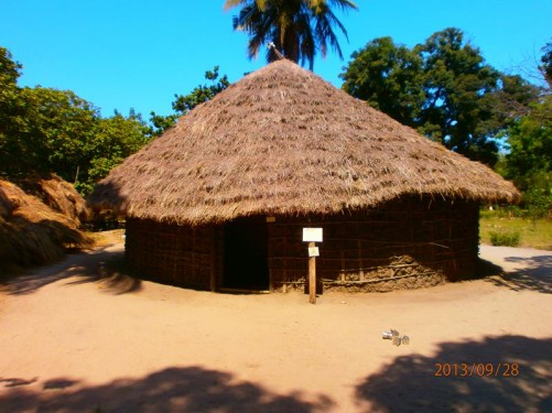 Outside a round hut with a straw roof and walls made of wood and dried mud.