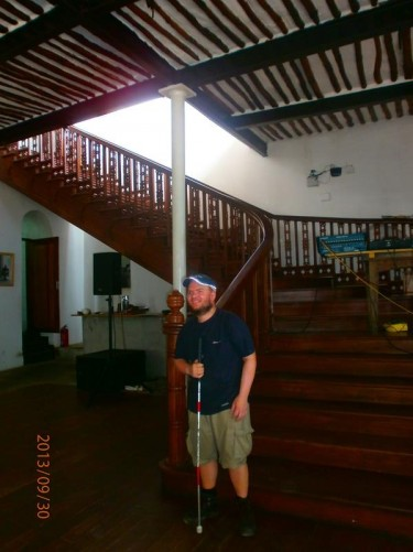 Inside David Livingstone's House. Tony at the bottom of a wooden staircase.
