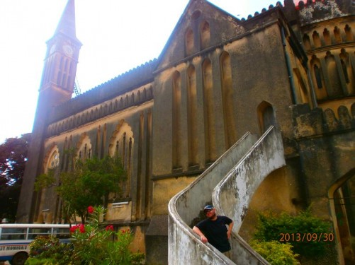 Again Tony on the steps. This time looking towards a clock tower and spire at the far end of the cathedral.