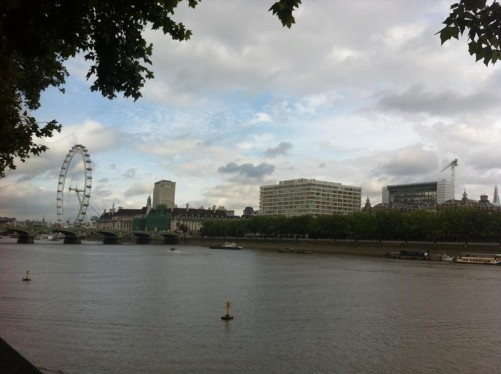 View along the River Thames from the north bank towards Westminster Bridge and the London Eye Ferris wheel.