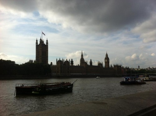 The Palace of Westminster from the south bank of the Thames. Barges and other boats on the river.