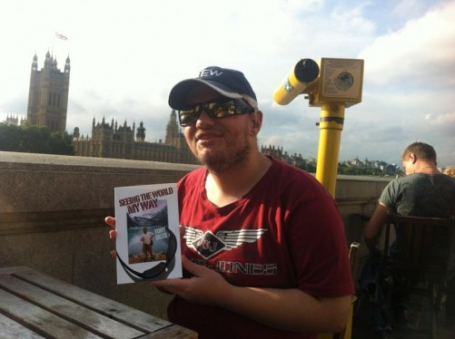 Tony sitting by the River Thames holding his book 'Seeing the World My Way'. The Palace of Westminster in the background.