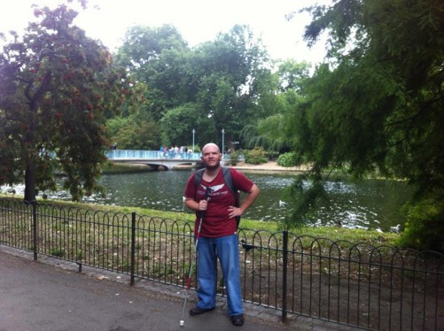 Tony by railings at the side of the lake. A footbridge (known as the Blue Bridge) over the lake behind.