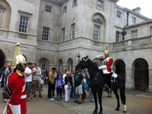 A Changing the Guard ceremony taking place. There is a ceremonial guard on horseback saluting and another standing to attention in front. A crowd of people watching.