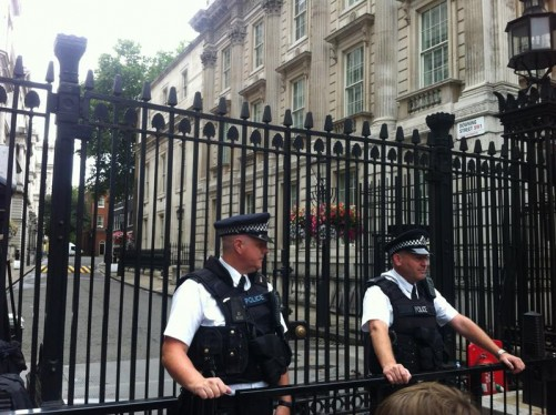 Two policemen guarding the Downing Street gates. A small part of the Prime Minister's residence, 10 Downing Street, can just be seen at the far end of the street.