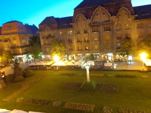 Looking down into Victory Square from Downtown Hostel Timișoara. There is an area of grass and flower beds in the centre. Taken during the evening.