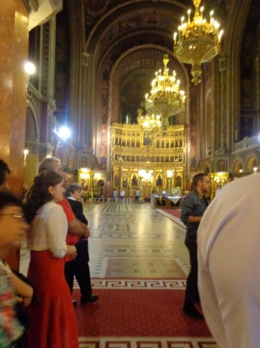 A group taking a tour inside the cathedral. View down the central aisle to the golden main altar at the far end.